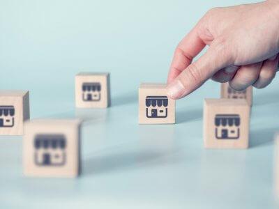 Vários blocos de madeira com lojas desenhadas esplhadas sobre uma superfície e mão feminina pegando um deles. Imagem ilustrativa texto empreender com franquias.