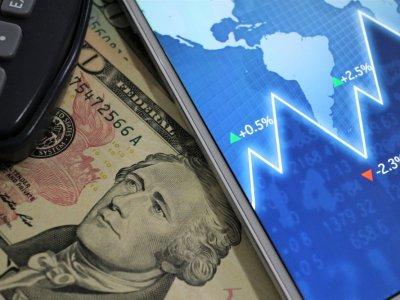 Dólares a baixo de um celular com gráficos e calculadora. Imagem ilustrativa texto empresa lucrativa
