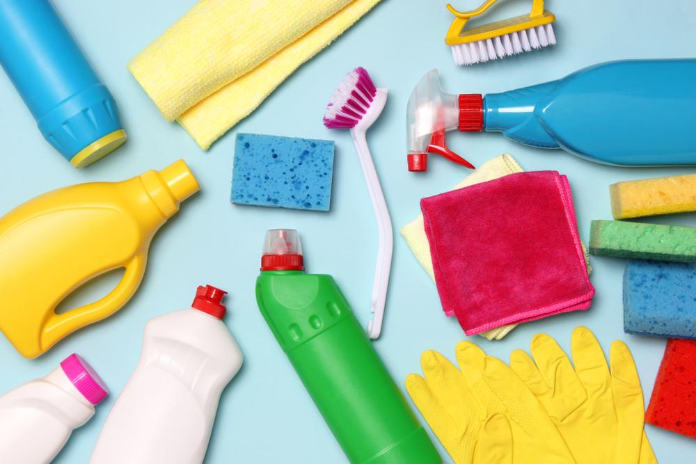 Vemos vários produtos e equipamentos para realização de limpeza: buchas, luvas, panos, escovas, frascos de detergente, desinfetante, amaciante e borrifador (imagem ilustrativa). Texto: franquia de serviço de limpeza.