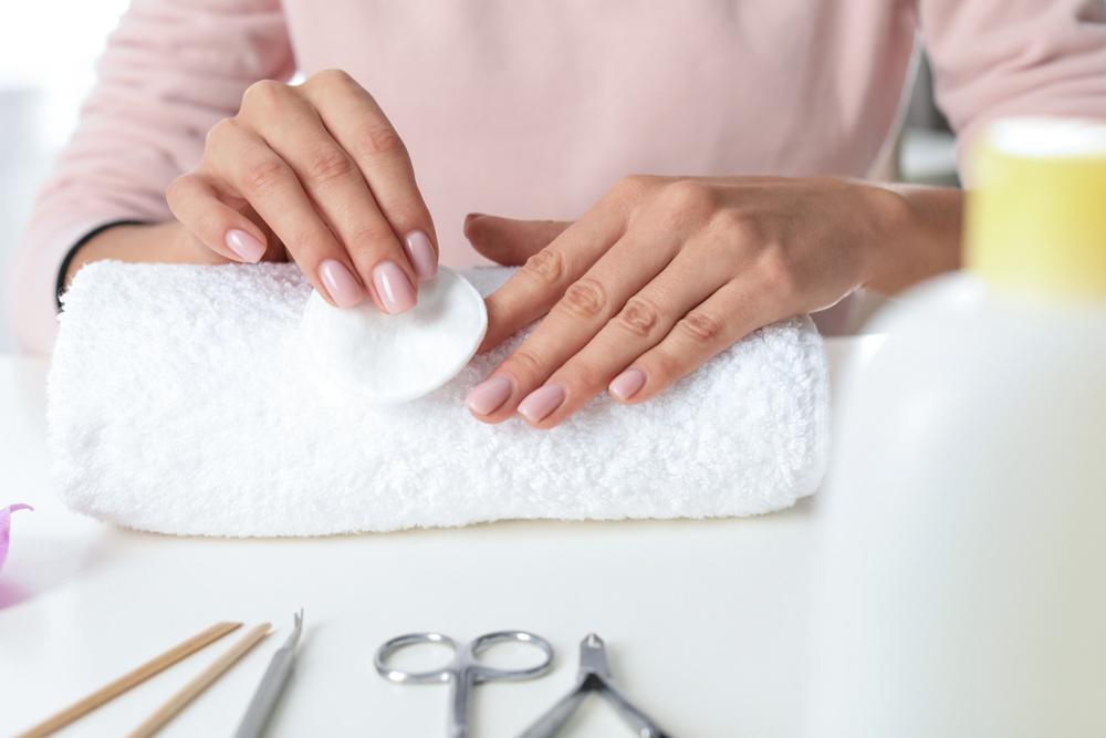 Mulher removendo esmalte de uma das suas mãos com equipamentos especializados.