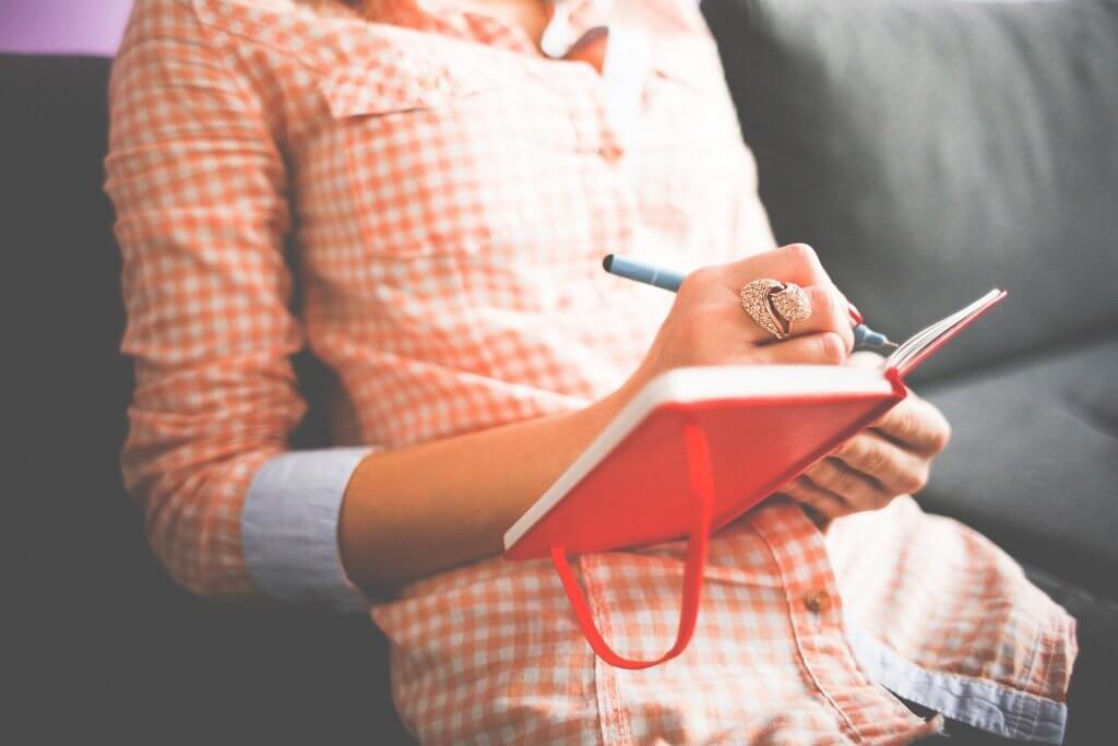 Foto de uma mulher com blusa xadreza laranja, sentada em um sofá cinza enquanto faz anotações em um caderno vermelho.