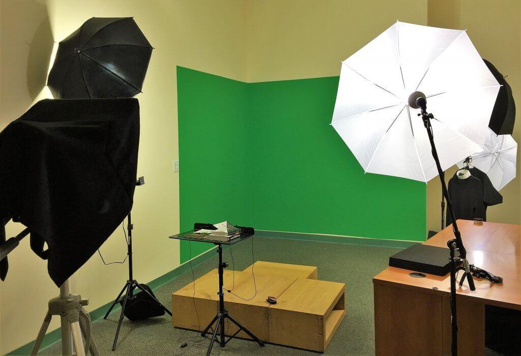 Foto de um estúdio de filmagem com paredes claras e tela verda. Temos bancos e móveis beges. Equipamentos de câmeras e luz pretos.