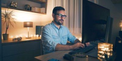 Homem trabalhando de casa em frente ao computador. Imagem ilustrativa texto franquia corretora de seguros home office