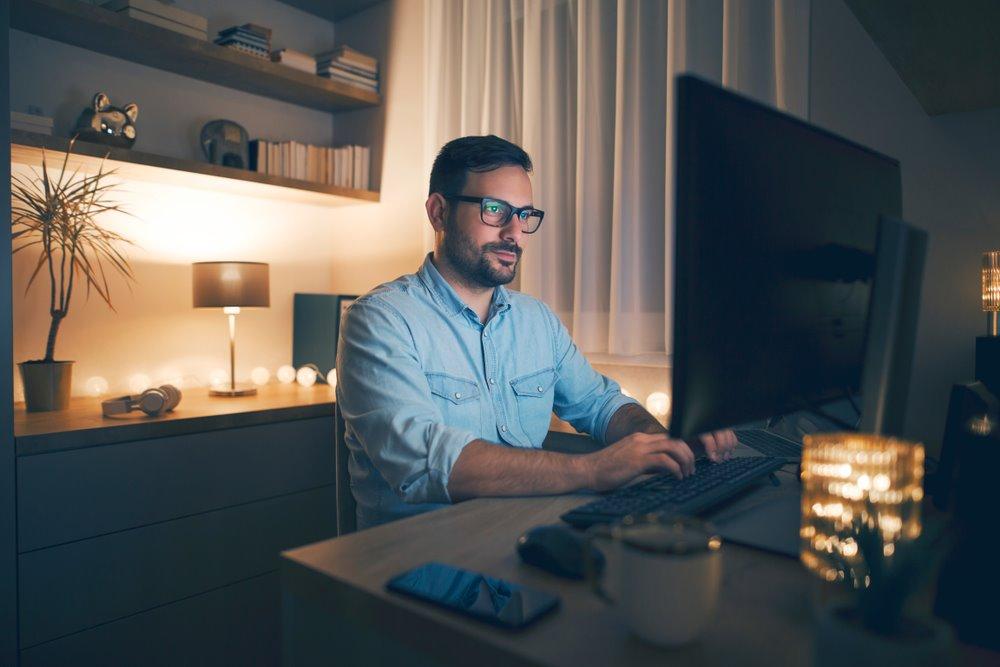 Vemos um homem trabalhando em sua casa. Ele está em seu escritório, em frente a um computador. É noite. Ele tem abajures e pequenas lâmpadas-luminárias acesas. Seu semblante é sério e determinado. Alguns objetos que podemos notar: uma estante com objetos e livros, um headphone e celular sobre a mesa (imagem ilustrativa). Texto: montar um negócio lucrativo.