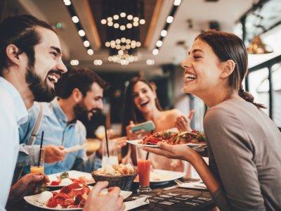 Casais em uma mesa de restaurante. Casal em destaque se olhando com um prato de comida. Imagem ilustrativa texto franquia de alimentação