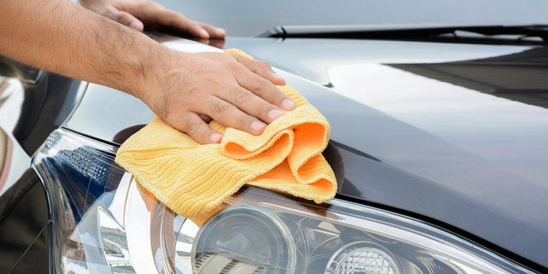 Homem passando flanela sobre o capô do carro. Imagem ilustrativa texto franquia de lava rápido