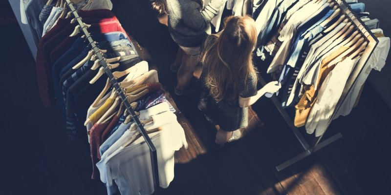 Varias roupas expostas em uma arara. Imagem ilustrativa texto franquia de loja de roupa