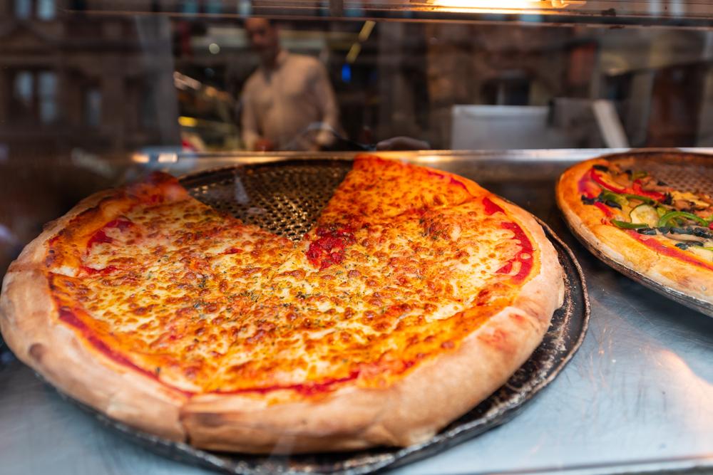 Vemos duas pizzas em um local que pode ser identificado como uma vitrine (imagem ilustrativa). Texto: franquias de pizzaria.