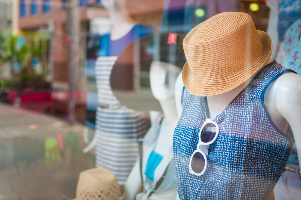 Vemos uma vitrine de roupas. Há um manequim estilo moda praia: vestido azul estampado, com detalhes em amarelo; óculos de sol e chapéu praia pardo (imagem ilustrativa). Texto: como ganhar dinheiro com franquia.