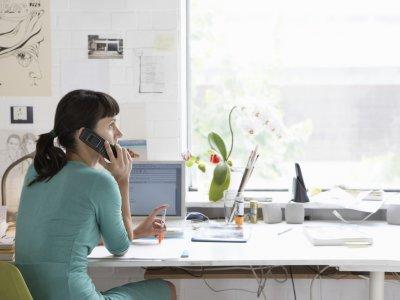 Mulher conversando ao telefone em frente ao computador. Ambiente como sua casa. Imagem ilustrativa texto franquia home office.