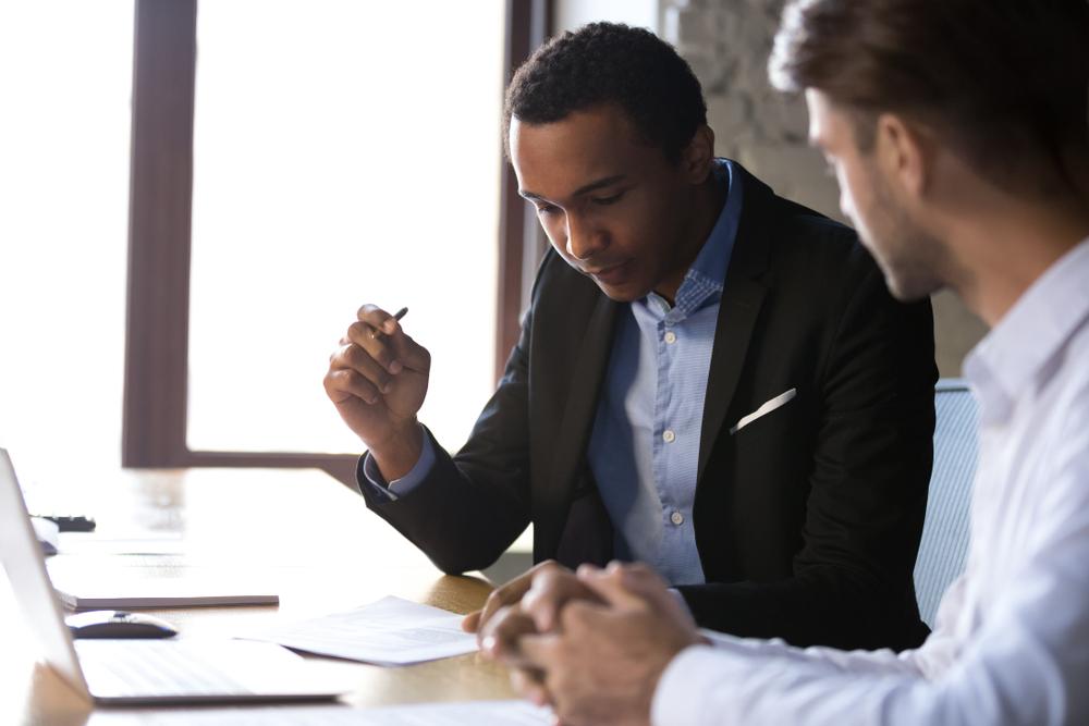 Vemos dois homens em uma, à mesa, com notebook, bloco de papel e o que parece ser um contrato.  Eles conservam enquanto um deles, um homem negro vestindo roupa social, lê esse contrato e segura uma caneta na mão direita (imagem ilustrativa). Texto: franquia corretora de seguros home office.