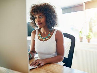 Mulher mexendo no computador em sua casa. Imagem ilustrativa texto franquias baratas e rentáveis