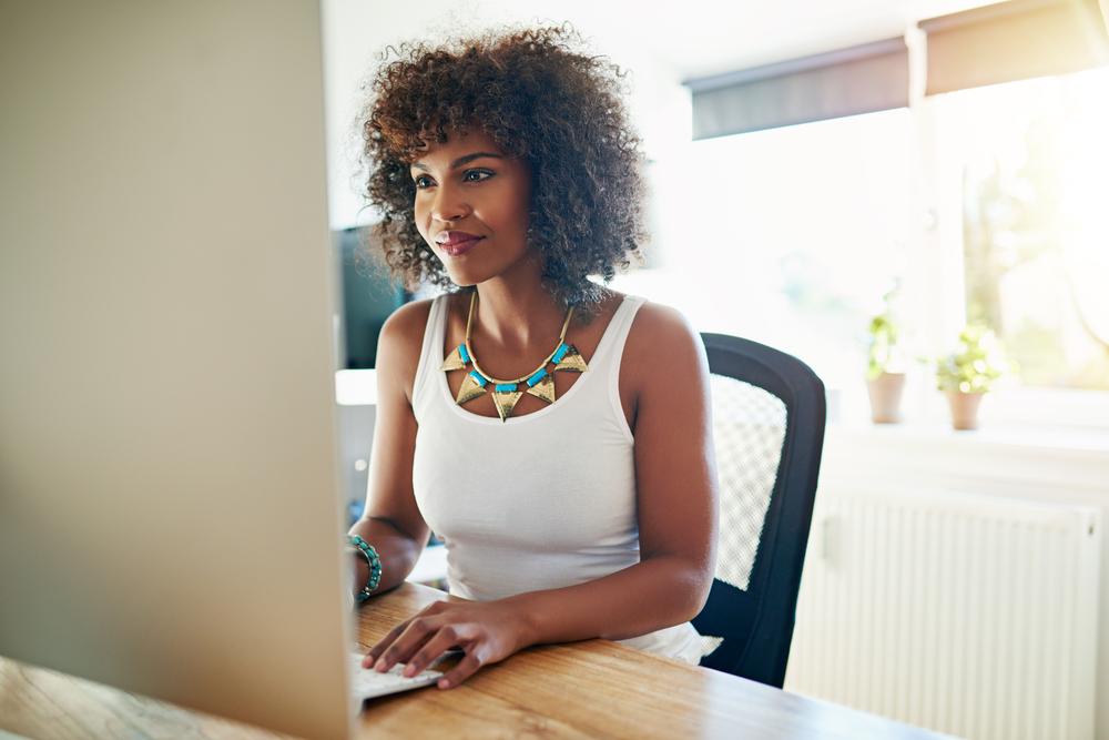 Uma mulher negra, muito bem vestida, está em sua casa, nos aparenta. Ela está de frente para o seu computador, realizando uma pesquisa, ao que parece, com um leve sorriso no rosto (imagem ilustrativa). Texto: montar um negócio lucrativo.