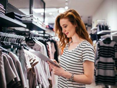 Mulher analisando dados da sua loja em frente a uma arara de roupas. Imagem ilustrativa texto franquias de moda