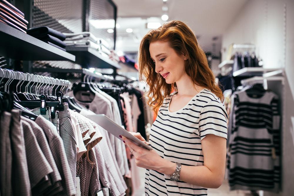 Vemos uma mulher com um tablet na mão analisando algumas peças de roupa de seu estoque (imagem ilustrativa). Texto: franquia de loja de roupa.
