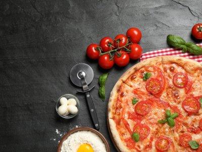 Pizza de marguerita exposta sobre uma mesa preta com alguns tomates ao lado. Imagem ilustrativa texto franquias de pizzaria