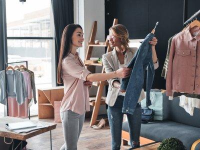 Mulheres olhando roupa em uma loja. Imagem ilustrativa texto franquias de roupa