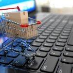 Carrinho de compras em miniatura sobre um teclado de notebook. Imagem ilustrativa texto franquias on-line.