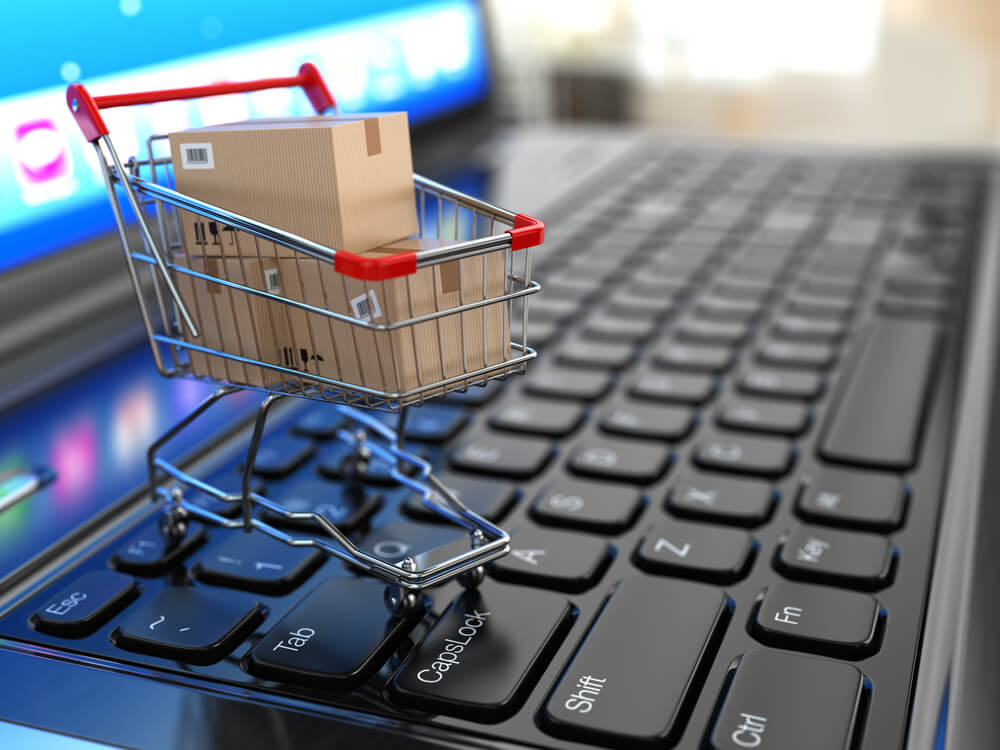 Vemos uma miniatura de um carrinho de compras, cheio de caixas de papelão lacradas, sobre um teclado de notebook (imagem ilustrativa). Texto: franquia bellaza.
