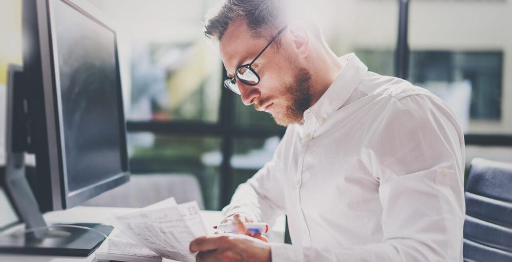 Um homem, de semblante concentrado, analisa uma série de documentos de frente para o seu computador.