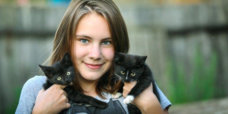 Menina de blusa azul segurando dois gatos pretos filhotes, ao fundo temos uma paisagem desfocada. Imagem ilustrativa para texto franquia Fórmula Animal vendas on-line.