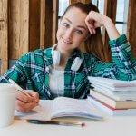 Foto de uma menina de blusa xadrez verde, com fones de ouvido branco no pescoço sentada em uma mesa com alguns livros empilhado na direita, um caderno aberto no centro e um copo de café na esquerda. Na mesa vemos algumas canetas e temos um fundo de madeira. Imagem ilustrativa para texto enjoy expansão.