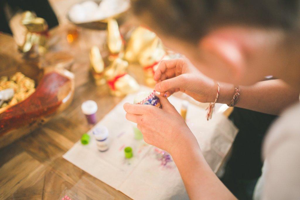 Foto de uma moça trabalhando com materiais em uma mesa de madeira desfocada. É possível ver vários objetos dourados e potes coloridos. Imagem ilustrativa para texto Franquia Flora Fiora Mercado DIY.