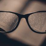 Foto de um óculos, enquanto ao fundo temos um livro. Apenas a imagem dentro das lentes é nítida. Imagem ilustrativa para texto Mercadão dos Óculos expansão.