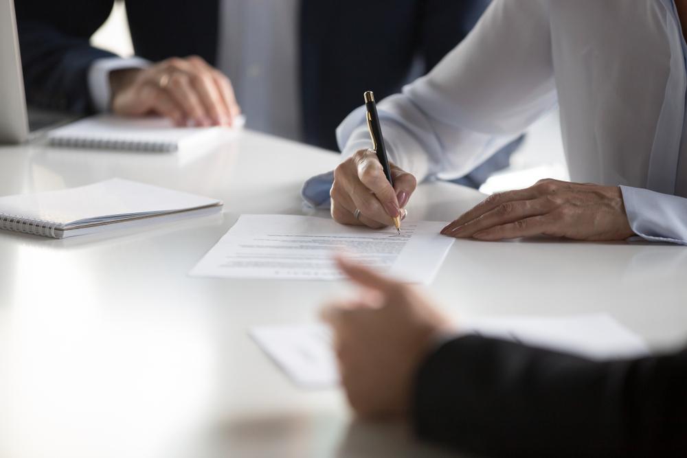 À mesa, uma mulher está assinando um contrato (imagem ilustrativa). Texto: modelo de negócio.