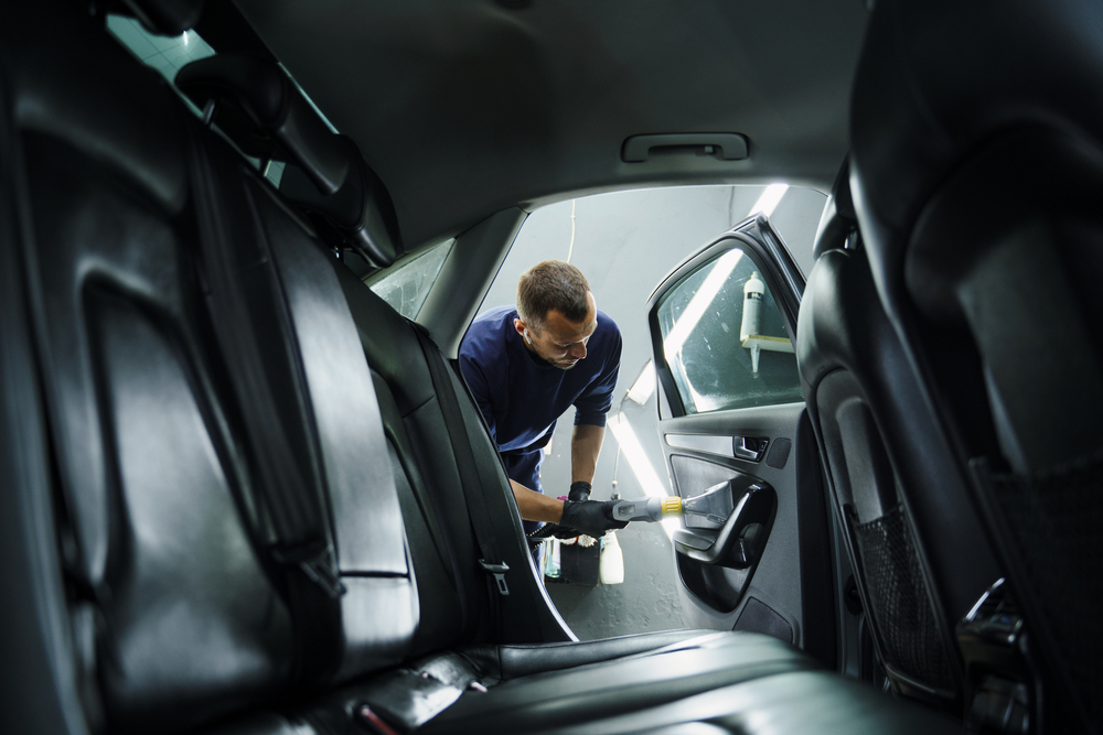 Vemos, na perspectiva do banco traseiro do carro, um homem realizar a limpeza da parte interna da porta traseira de um veículo