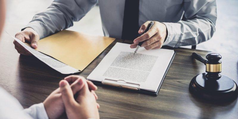 Juiz analisando documento com martelo ao lado e uma pessoa em frente. Imagem ilustrativa texto lei de franquia
