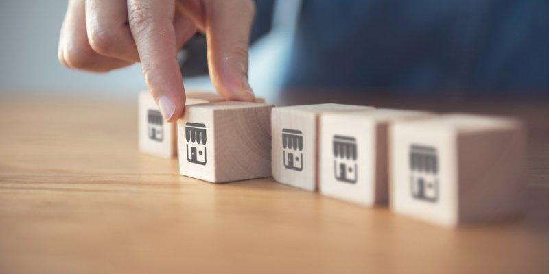 Bloco de madeira representando as microfranquias e um deles sendo destacado por uma pessoa. Imagem ilustrativa texto microfranquias