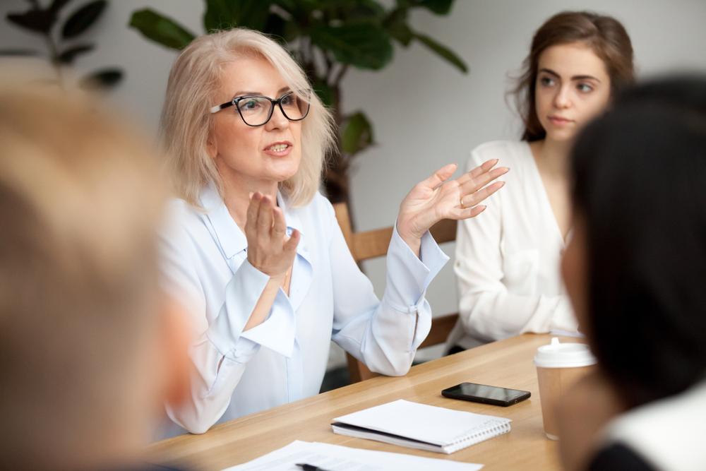 Mulher bastante elegante conversa com outras pessoas em uma reunião. Ela está usando seus óculos de grau com armação de gatinho (imagem ilustrativa). Texto: franquias brasileiras.