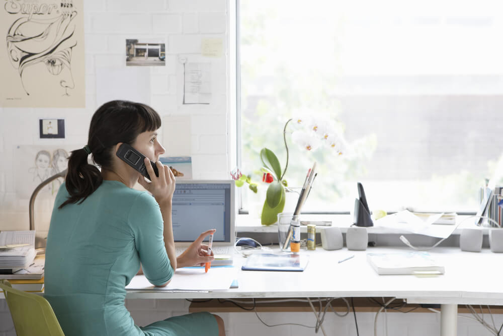 Mulher conversa ao telefone em seu escritório particular em casa (imagem ilustrativa). Texto: franquias on-line.