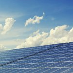 Foto de uma placa utilizada para a obtenção de energia solar. Ao fundo vemos um céu azul com nuvens. Imagem ilustrativa para texto Solarprime diminuição de custos.