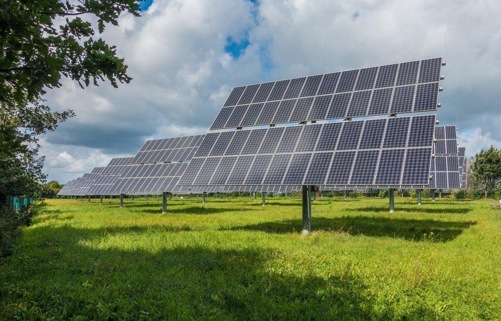 Vemos vários painéis solares espalhados por um campo aberto. Temos grama, árvores ao redor e o céu com nuvens. Imagem ilustrativa para texto Solarprime diminuição de custos.