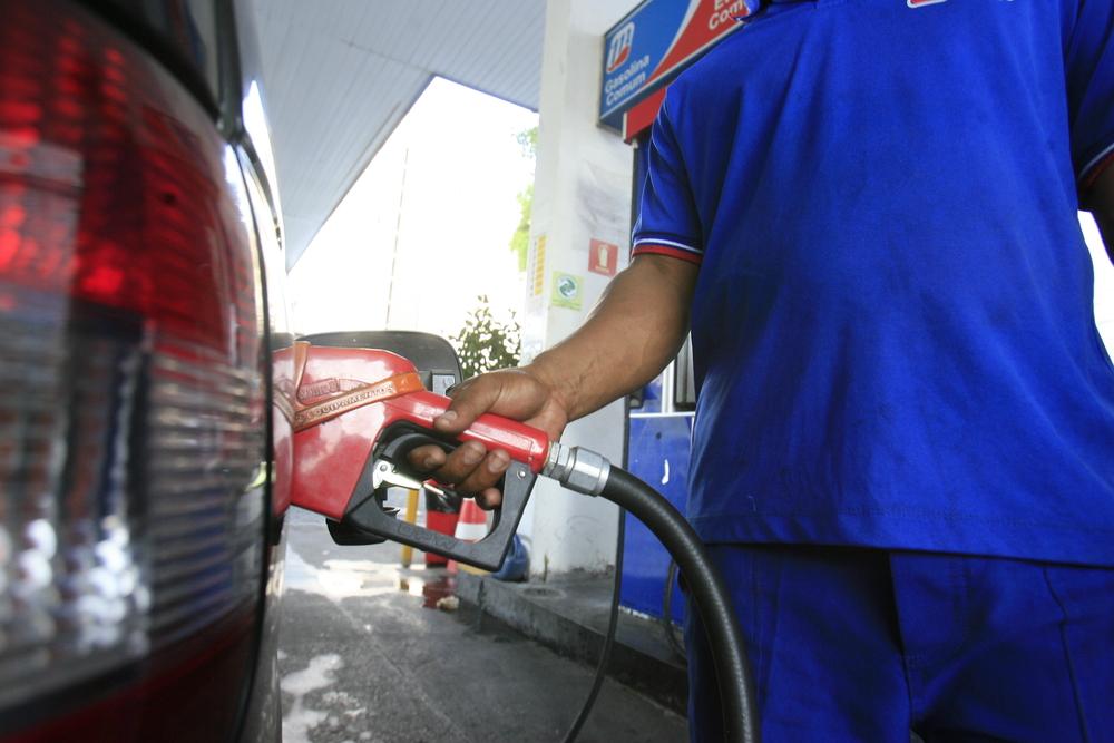 Vem em close a mão de um frentista de posto de gasolina que abastece um carro (imagem ilustrativa). Texto: franquia de posto de combustível.