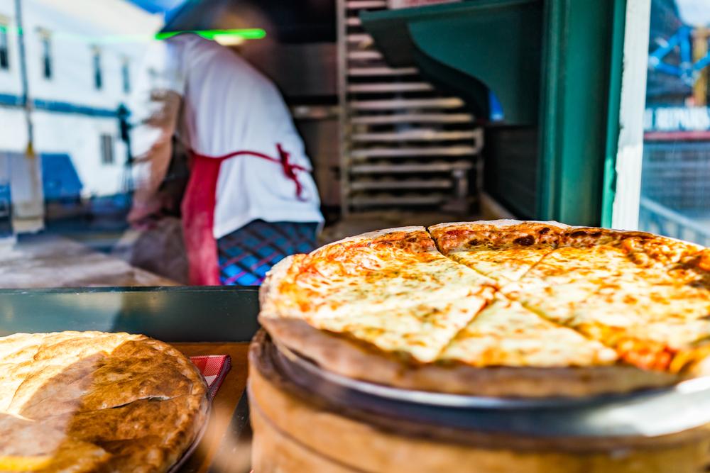 Vemos uma pizza exposta em outra vitrine enquanto o pizzaiolo está ao fundo.