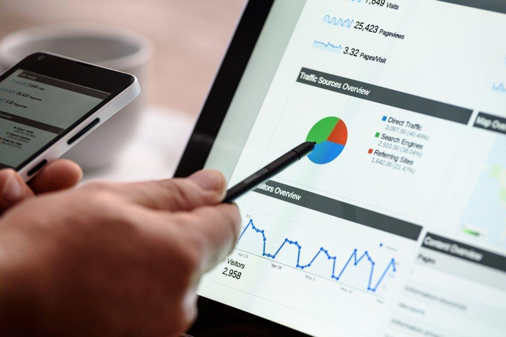 Homem apontando gráficos ligados ao marketing digital em seu computar.