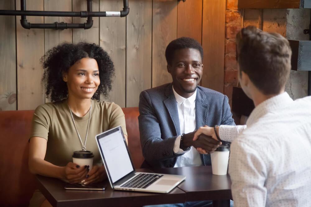 Um casal jovem aparenta estar acompanhado de um representante comercial. Os dois homens apertam as mãos e parecem fechar um negócio (imagem ilustrativa). Texto: empreender em franquias.