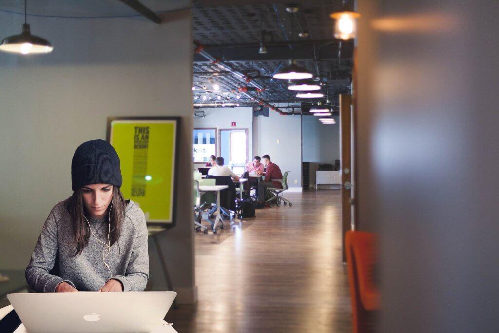 Uma jovem de blusa cinza e touca preta, está sentada de frente para o seu computador, enquanto, ao fundo, outras pessoas participam de uma reunião.