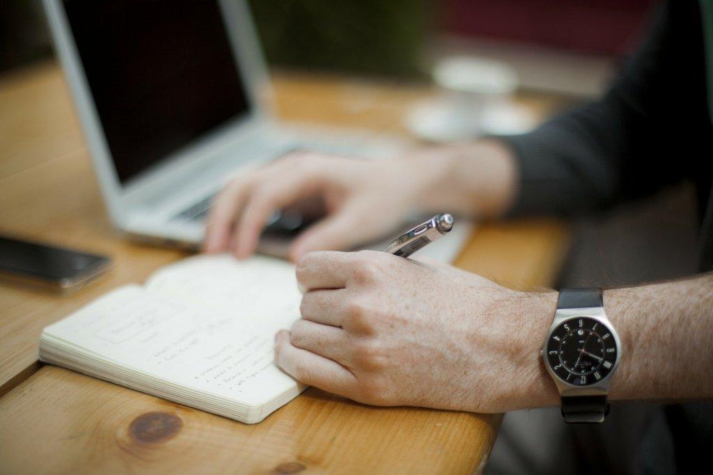 Foto da mão de um homem com relógio preto, segurando uma caneta prata enquanto escreve em um caderno. Temos uma mesa de madeira, com um computador, celular e xícara ao fundo. Imagem ilustrativa para texto Solarprime diminuição de custos.