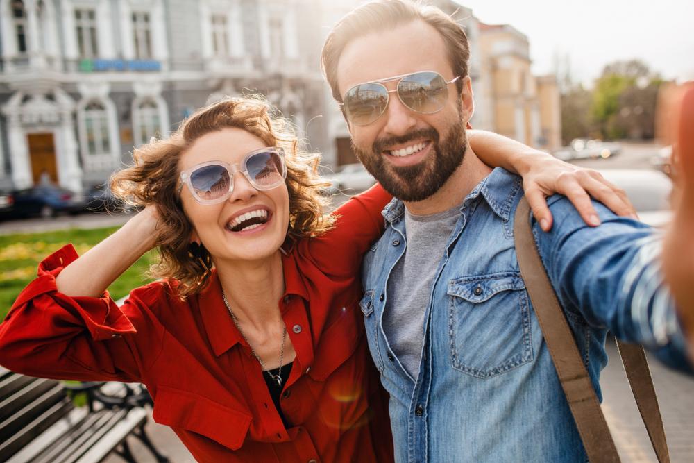 Casal de óculos tirando foto feliz durante um passeio.
