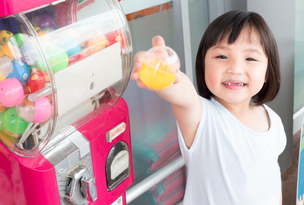 Vemos uma menina ao lado de uma vending machine, sorrindo e com uma surpresa à mão (imagem ilustrativa). Texto: franquia público infantil.