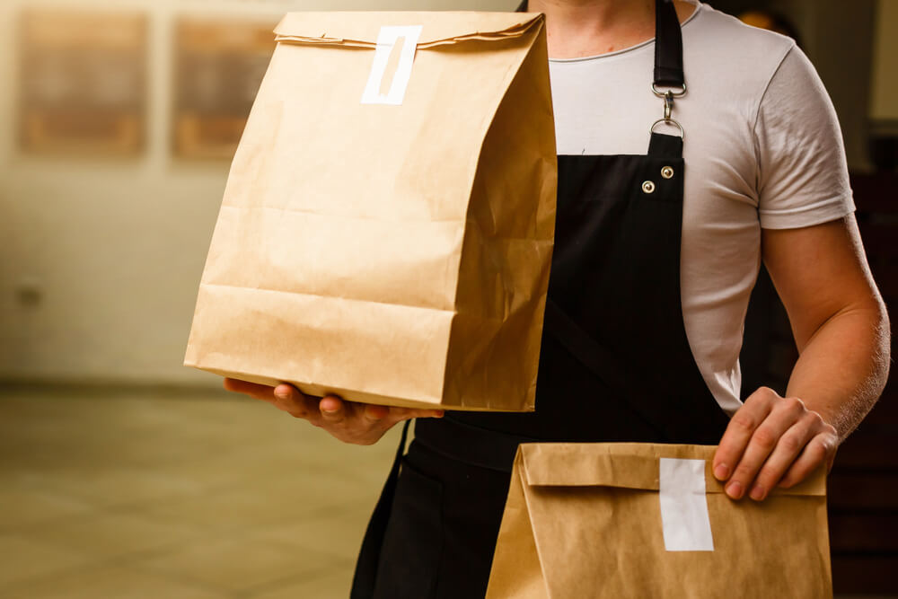 Vemos um homem carregando duas embalagens para serem entregues (imagem ilustrativa). Texto: franquia de delivery.