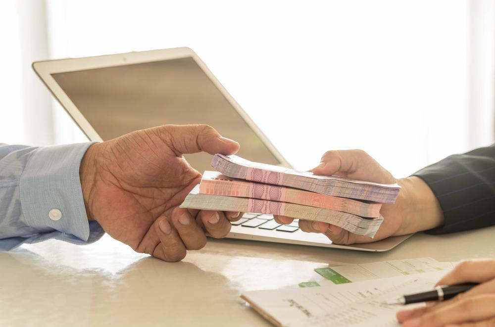 Vemos em perspectiva a mão de dois homens. Um deles repassa ao outro três bolos de notas de dinheiro.