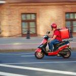Entregador sobre a moto andando para fazer a entrega com encomenda nas costas. Imagem ilustrativa texto franquia de delivery