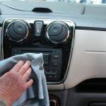 Homem fazendo a limpeza interna de um veículo com flanela. Imagem ilustrativa texto franquia de lavagem de veículos a seco