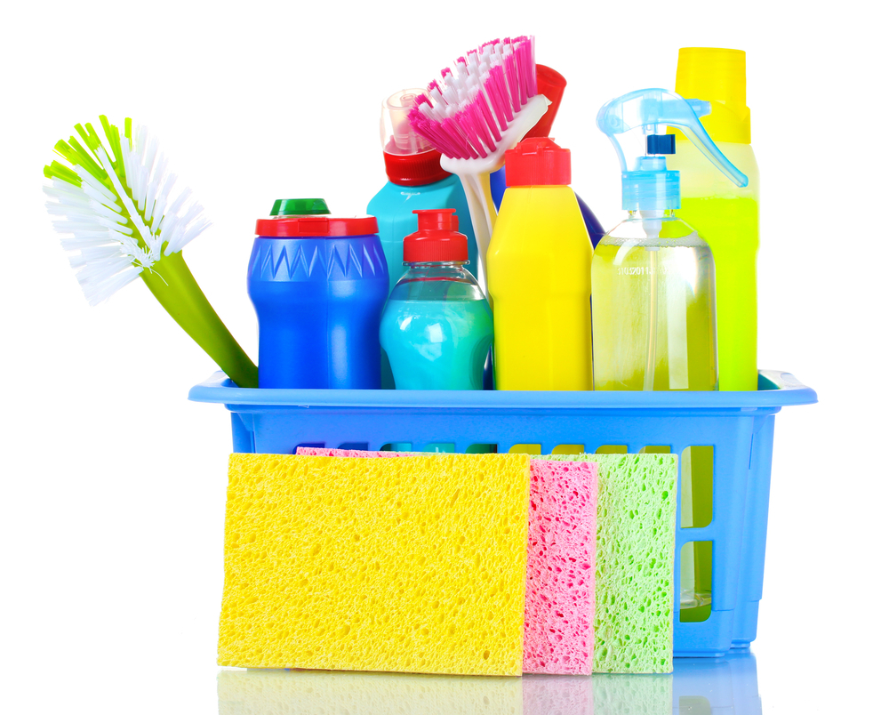 Vemos alguns materiais de limpeza dentro de um cesto. Temos três buchas vegetais em amarelo, rosa e verde escoradas do lado de fora.