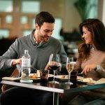 casal comendo macarrão num restaurante com vinho e garrafa de vinho ao lado. Imagem ilustrativa texto franquia de restaurante